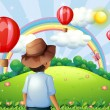 A boy at the hilltop with flying balloons and a rainbow — Stock Vector