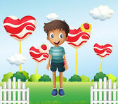 A smiling young boy standing in the garden with giant heart loll — Stock Vector