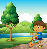 A kid at the riverbank playing with his bicycle — Stock Vector