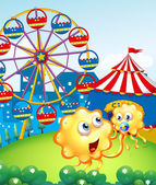 A baby monster with her mother at the hilltop with a carnival — Stock Vector