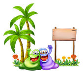 Two monsters having fun in front of the empty wooden signboard — Stock Vector