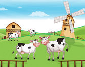 Cows at the hilltop with a windmill — Stock Vector