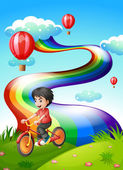 A boy biking at the hilltop with a rainbow — Stock Vector