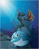 A smiling shark under the sea near the rocks — Stock Vector