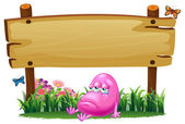 A pink beanie monster under the empty wooden signboard — Stock vektor