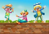 Three clowns above the wall — Stock Vector