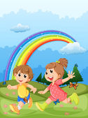 Kids playing at the hilltop with a rainbow in the sky — Stock Vector