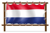 The flag of Netherlands attached to the wooden frame — Stock Vector