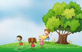 Kids playing at the hilltop near the tree — Stock Vector