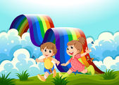 Happy kids playing at the hilltop with a rainbow — Stock Vector