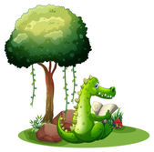 A crocodile reading beside the tree — Stock Vector
