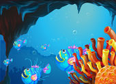 A cave under the sea with a school of fish — Stock Vector