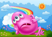 A tired pink monster at the hilltop with a rainbow in the sky — Stock Vector