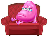 A crying monster sitting on a red sofa — Stock Vector