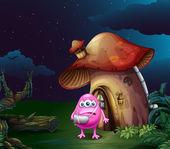 An injured pink monster near the mushroom house — Stock Vector
