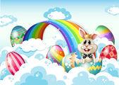 A king bunny at the sky with Easter eggs near the rainbow — Stock Vector