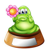 A green monster holding a flower — Stock Vector