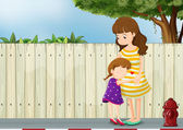 A mother and her daughter near the fence at the road — Stock Vector