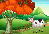 A smiling cow near the big tree — Stock Vector