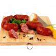 A few smoked sausages on a wooden board — Stock Photo