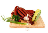 Long and thin smoked sausages on a wooden board — Stock Photo