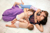 Breast feeding two little sisters twin girls at the same time. — Stock Photo