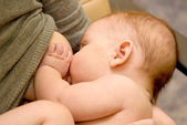 Newborn baby is breast feeding — Stock Photo