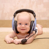 Newborn baby boy with blue eyes smiling wearing a headset. — Stock Photo