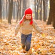 Kid running and smiling in autumn forest — Stock Photo