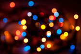 Blurred colorful circles bokeh of Christmaslight against dark background — Stock Photo