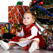 Baby sitting under a Christmas tree — Photo