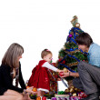 Family - father mother and baby daughter in a smart dress decorating Christmas tree — Stock Photo #12849450
