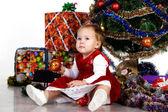 Dítě sedí pod vánoční stromeček — Stock fotografie