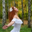 Red-haired young woman head looking up, arms. as if flying — Stock Photo
