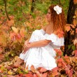Red-haired young woman, wearing in white dress or the bride - Stock Photo