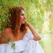 Beautiful young red-haired woman in white dress — Stock Photo