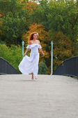 Red-haired young woman, wearing in white dress or bride running across a bridge — Stock Photo