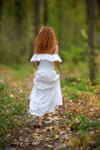Bride go to the forest, view from the back. The rear view. — Stock Photo