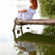 Bride or undine sitting on a wooden bridge — Stock Photo