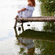 Bride or undine sitting on a wooden bridge — Stock Photo #13591180