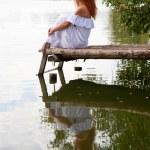 Bride or undine sitting on a wooden bridge — Stock Photo