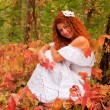 Young woman sitting among red leaves in autumn forest. — Stock Photo