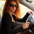 Red-haired woman driving car — Stock Photo