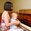 Baby is learning to play the piano. — Stock Photo #13612322