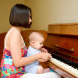 Baby is learning to play the piano. — Stock Photo