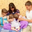 Breast feeding two little sisters twin girls at same time — Stock Photo