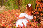 Woman sitting among red leaves in autumn forest. — Stock Photo