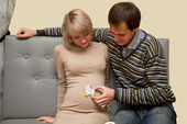 Happy future parents putting cookie to tummy — Stock Photo