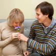 Man giving his pregnant wife a bouquet of flowers — Stock Photo #13733850