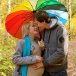 Happy pregnant woman and man walking in autumn forest — Stock Photo